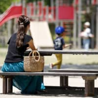 A single mother sits on a bench at a park in Sendai. Single moms and female nonregular workers have been hit hardest by the recent rise in unemployment. | KYODO