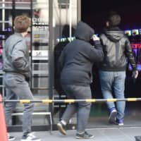 In a photo taken May 1, people walk into a pachinko parlor in Kobe that remained open even after the Hyogo Prefectural Government requested it temporarily shut down. | KYODO