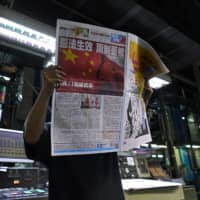 A worker checks a copy of Apple Daily's Wednesday edition seen with its front page title of 'Draconian law is effective, one country two system is dead' at the newspaper's printing house in Hong Kong. | AP