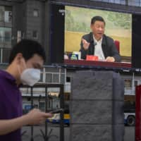 A large video screen shows Chinese President Xi Jinping speaking in Beijing on Tuesday.   AP / VIA KYODO