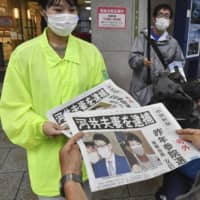 A woman hands out copies of a newspaper in Hiroshima on June 18 reporting that former Justice Minister Katsuyuki Kawai and his wife, Anri, had been arrested earlier in the day on suspicion of giving out cash to local politicians and supporters during her 2019 Upper House election campaign.    KYODO