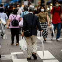 Shoppers take to the streets of Tokyo on Wednesday as economic activity continues to pick up after the state of emergency was lifted for the coronavirus. | AFP