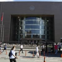 People walk outside a court in Istanbul Friday where the trial began for defendants accused of smuggling former Nissan Motor Co. Chairman Carlos Ghosn out of Japan to Lebanon, via Turkey. | AP