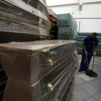 A worker sweeps up among coffins at the Rio Pax funeral company in Rio de Janeiro on Friday. | REUTERS