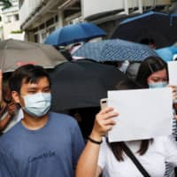 Supporters raise white paper to avoid slogans banned under the new national security law in Hong Kong on Friday.  | REUTERS