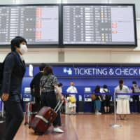 Airline passengers check in at Tokyo International Airport on Saturday. | KYODO