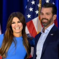 Donald Trump Jr. and his girlfriend, Kimberly Guilfoyle, smile during a news conference in Des Moines, Iowa, in  February.   AFP-JIJI
