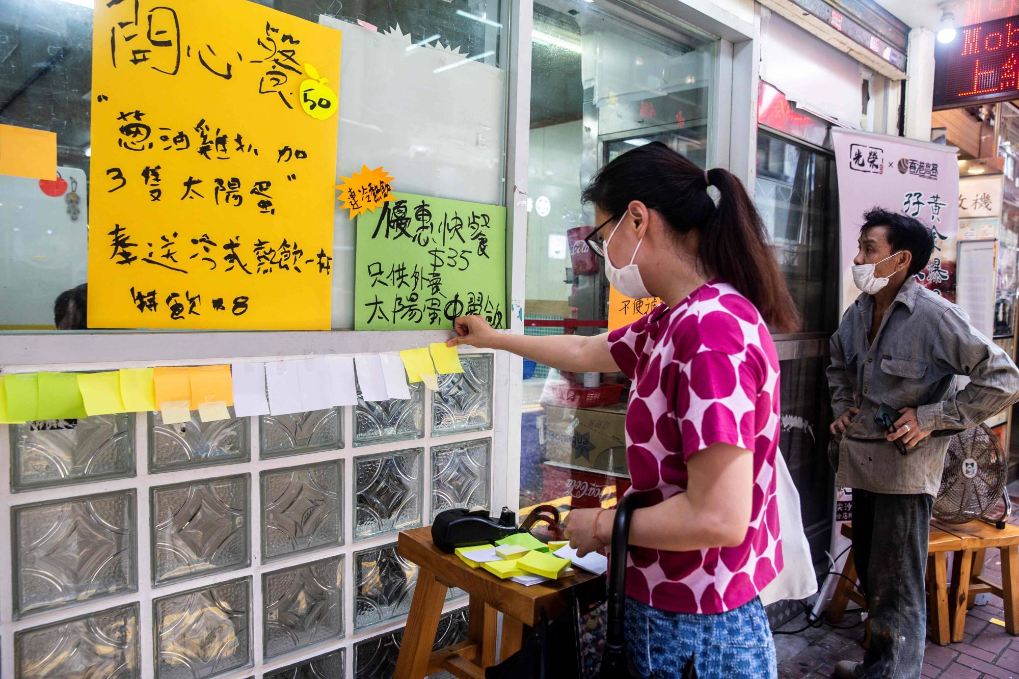 A woman sticks a blank note onto a 'Lennon Wall' outside a pro-democracy restaurant in Hong Kong on Friday.  | AFP-JIJI