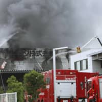 Some rises from a warehouse at a factory operated by household product maker Lec Inc. in the town of Yoshida, Shizuoka Prefecture, on Sunday. | KYODO