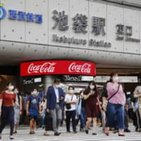 People walk in front of Ikebukuro Station in central Tokyo on Saturday afternoon.   KYODO