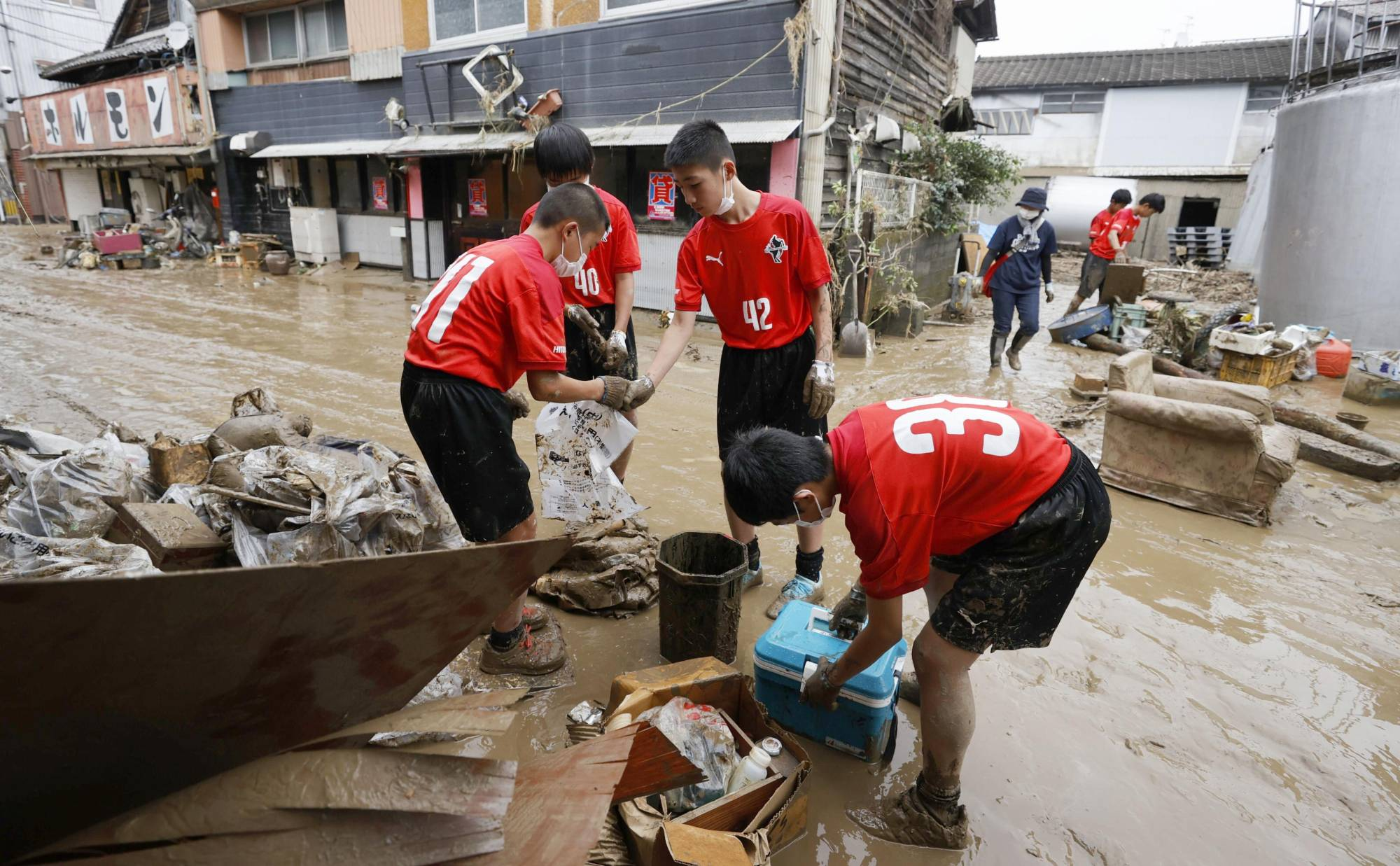 Boys from a local junior soccer team help clean up after mudslides hit Hitoyoshi, Kumamoto Prefecture, on Sunday. | KYODO