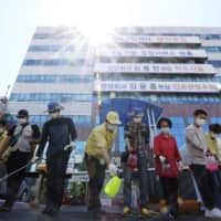 Health officials disinfect an area around a hospital after one of the hospital's patients tested positive for the new coronavirus in Gwangju, South Korea, on Wednesday. | YONHAP / VIA AP