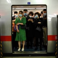 Passengers commute on a subway train during rush hour in Beijing.  | AFP-JIJI