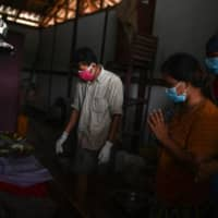 Htar Htar Myint (second from right) prays by the coffin of her husband, Than Naing, following the deadly landslide.   AFP-JIJI