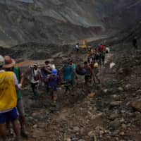 Bodies are recovered after the jade mine landslide in Hpakant on Thursday.   AFP-JIJI
