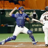 Dragons catcher Ariel Martinez throws to second on a stolen base attempt by the Giants' Naoki Yoshikawa during the sixth inning on Saturday at Tokyo Dome.  | KYODO