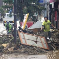 People work on cleaning up a street in Hitoyoshi, Kumamoto Prefecture, Monday after the area was flooded following torrential rain.   KYODO