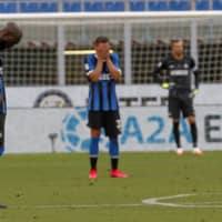 Inter's Romelu Lukaku (left) and Danilo D'Ambrosio (center) react after Bologna's second goal on Sunday in Milan. | AP