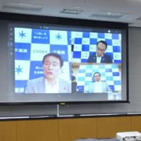 Economic revitalization minister Yasutoshi Nishimura attends a videoconference with the governors of Chiba, Kanagawa and Saitama on Sunday at the Cabinet Office in Tokyo to discuss measures to fight COVID-19. | KYODO