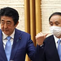 Prime Minister Shinzo Abe (left) and Chief Cabinet Secretary Yoshihide Suga have denied rumors that their long-standing working relationship is on the rocks. | AP / BLOOMBERG