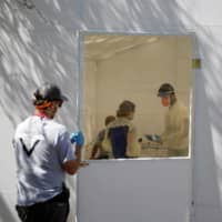 Medical staff from Global Response Management take samples from a patient suspected of contracting COVID-19 at a migrant encampment, where more than 2,000 people live while seeking asylum in the U.S., in Matamoros, Mexico, on May 1. | REUTERS