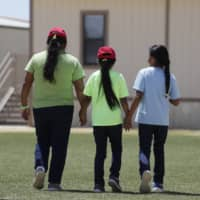Immigrants seeking asylum leave a cafeteria at the ICE South Texas Family Residential Center in Dilley, Texas. The isolation of at least three families at the site has raised new fears of the coronavirus spreading through a facility that has long been accused of providing substandard medical care.  | AP