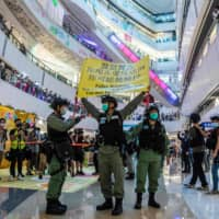 Riot police hold up a warning flag during a demonstration at a mall in Hong Kong on Monday. | AFP-JIJI