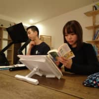 Crystal Pak, right, reads a book in a study room at a share house operated by Be Good Japan Inc. in Tokyo's Toshima Ward in March.  | KAZUAKI NAGATA