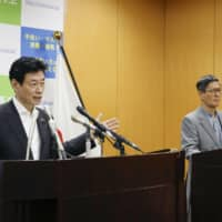 Economic revitalization minister Yasutoshi Nishimura speaks at a news conference in Tokyo on Monday, along with Shigeru Omi, the head of a new government panel on coronavirus measures. | KYODO
