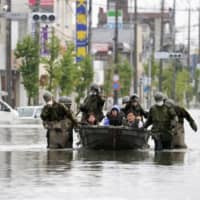 Self-Defense Forces rescuers carry residents by boat in flooded Omuta, Fukuoka Prefecture, on Tuesday. | KYODO