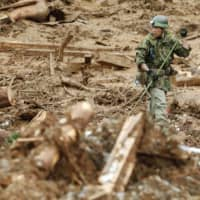 A Self-Defense Forces member searches for survivors in the mudslide-hit town of Tsunagi, Kumamoto Prefecture, on Tuesday. | KYODO