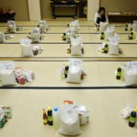 A Vietnamese migrant worker who lost her job amid the coronavirus outbreak prepares packages of food and protective masks for Vietnamese people in need that live in Japan, at a Buddhist temple in Tokyo on May 2. | REUTERS