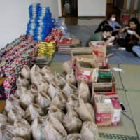 Vietnamese volunteers and migrant workers who lost their jobs amid the coronavirus outbreak eat lunch during a break on May 2 at a Buddhist temple in Tokyo that has turned into a shelter for young Vietnamese migrant workers. | REUTERS