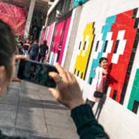 A woman poses for a photograph in front of a mural featuring characters from the Pac-Man video game in Hong Kong in February 2019. | BLOOMBERG
