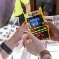Visitors examine a Pac-Man Micro Player during an electronics expo in Los Angeles in June 2019. | BLOOMBERG