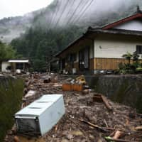 Debris lines a residential area hit by torrential rain in Ashikita, Kumamoto Prefecture, on Tuesday. | AFP-JIJI