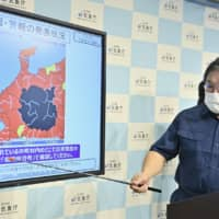A Meteorological Agency official discusses the emergency rain warning issued for parts of Nagano and Gifu prefectures during a news conference on Wednesday morning.  | KYODO