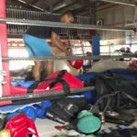 Boxer Sewon Okazawa removes damaged equipment from the ring on Tuesday at his gym in Kanoya, Kagoshima Prefecture, after it was hit by flooding.   KYODO