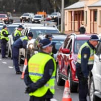 Police in the southern New South Wales border city of Albury check cars crossing the state border from Victoria on Wednesday after authorities closed it due to an outbreak of COVID-19 in Victoria. | AFP-JIJI