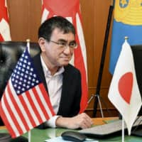 Defense Minister Taro Kono attends a videoconference with his American and Australian counterparts at the ministry Wednesday. | DEFENSE MINISTRY / VIA KYODO