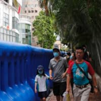 People walk past water-filled barriers after the opening ceremony for a national security office in Hong Kong.  | REUTERS