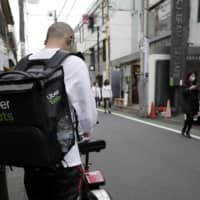 Dining delivery: Uber comes to Tokyo having already found success with its Uber Eats food delivery service. | BLOOMBERG
