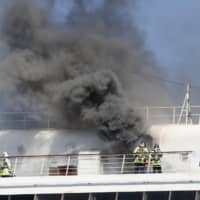 Smoke rises from the Japanese cruise ship Asuka II, docked in Yokohama Port, on June 16. Finding places to park idle ships is just the first painful point. To keep things shipshape and avoid costly repairs and other issues, the vessels must also be kept operating. | AP