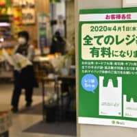 Going up: A sign tells shoppers that the store will now charge for all plastic bags.  | KYODO