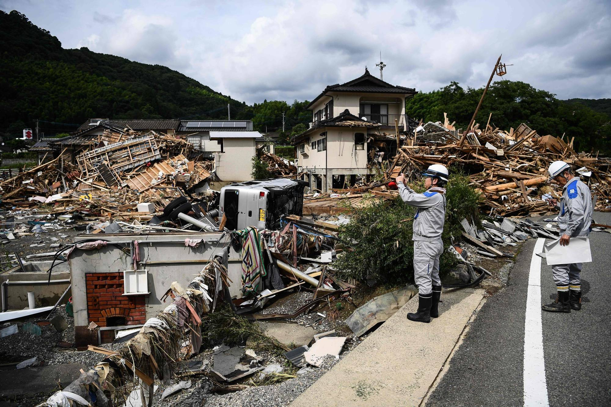 Workers survey the devastation following days of heavy rain and flooding in the village of Kuma, Kumamoto Prefecture, on Wednesday. Four major Japanese nonlife insurers' plan to raise insurance premiums for homes follows a rise in insurance payouts on the back of a series of natural disasters across the country. | AFP-JIJI