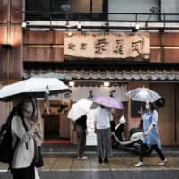 Pedestrians wearing protective masks pass a restaurant in the Shinjuku district of Tokyo on June 14. Sentiment among people working in industries particularly susceptible to changes in economic trends recorded the biggest-ever monthly increase in June, according to a government report.    BLOOMBERG