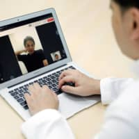 Medical doctor Makoto Kitada demonstrates a telemedicine application service called 'CLINICS', developed by medical start-up Medley Inc., in Tokyo on Wednesday. | REUTERS