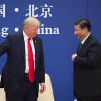 U.S. President Donald Trump and Chinese President Xi Jinping speak during a business leaders event in Beijing in November 2017.  | AFP-JIJI