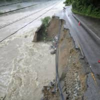 Some roads, such as this one in Takayama, Gifu Prefecture, have been destroyed by rivers having broken their banks. | KYODO