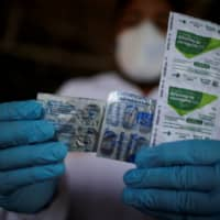 A health care worker holds a packet of hydroxychloroquine sulfate, azitrophar and chloroquine diphosphate at the riverside community of Santo Ezequiel Moreno in Brazil. | REUTERS